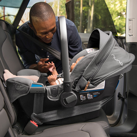 a man viewing a baby in the Nuna Pipa RX and Relx Base car seat