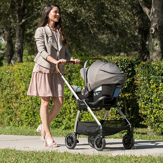 a woman pushing a baby in a Nuna stroller, Kidsland baby gear